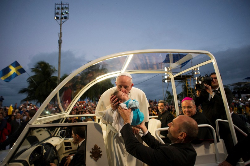 Pope Francis kisses an infant as he makes his way to Copacabana beach for the World Youth Day Way of the Cross service in Rio de Janeiro on 26 July, 2013. Photo: CNS/L'Osservatore Romano
