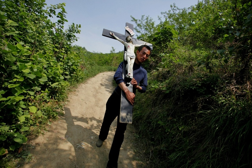 In this 2013 file photo, a Chinese Catholic carries a crucifix during a pilgrimage in the Shaanxi province of China. Hong Kong Cardinal John Tong Hon has asked Communist Party chiefs in Beijing to order a halt to an ongoing cross-removal campaign from churches in Zhejiang province. Photo: CNS/Wu Hong, EPA