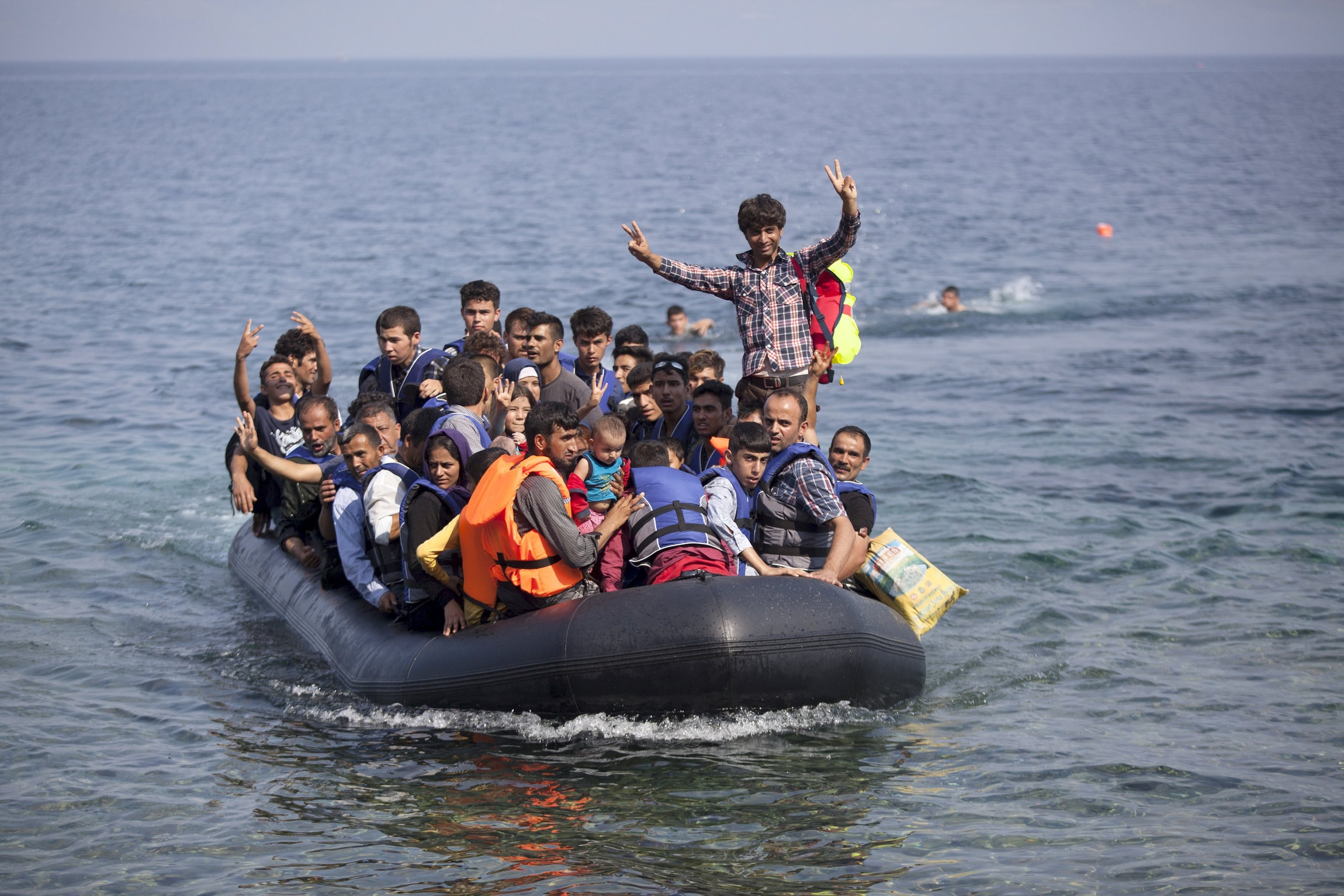 Syrian and Afghan refugees on a dinghy wave as they approach the Greek island of Lesbos on 3 September. The International Organisation for Migration says 1500-2000 refugees are taking the route through Greece, Macedonia and Serbia to Hungary every day. The number is expected to rise to 3000.  Photo: CNS/Dimitris Michalakis, Reuters