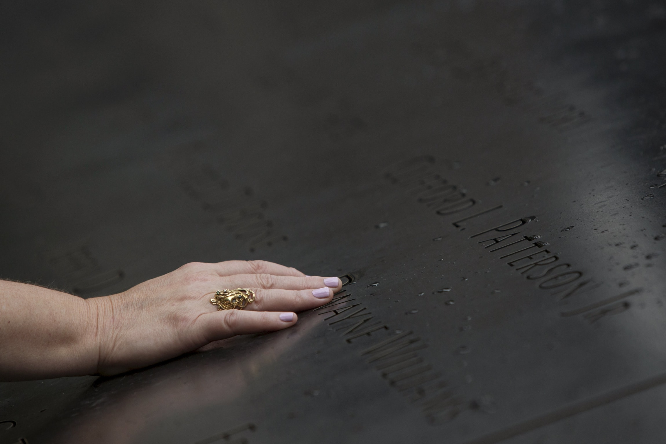 A woman touches the names at the National September 11 Memorial and Museum in New York City. The 2001 terrorist attacks claimed the lives of nearly 3000 people in New York City, Shanksville, Pennsylvania, and at the Pentagon. Photo: CNS/Andrew Kelly, Reuters