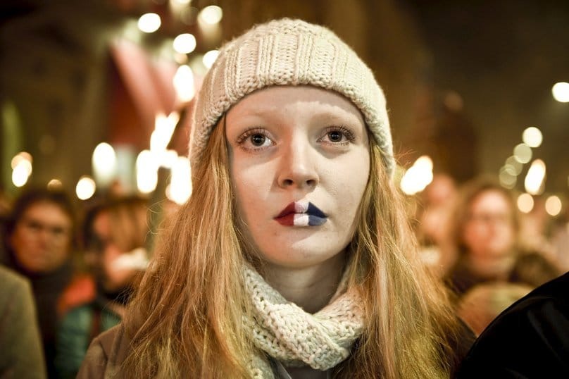 A girl with her lips painted in the French colors attends a commemorative event in front of the French Embassy in Copenhagen, Denmark, on 15 November. Photo: CNS/Nils Meilvang, Reuters