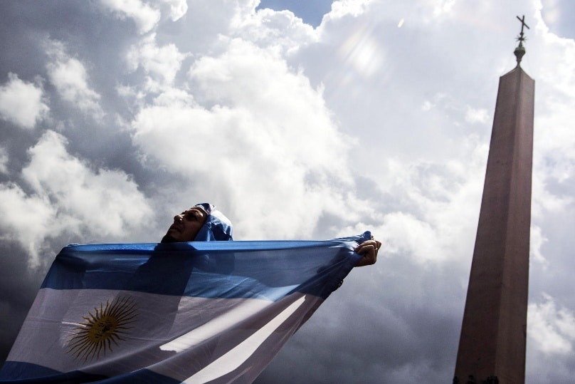 A man holds an Argentine flag at the Vatican in this 2014 file photo. Photo: CNS/Angelo Carconi, EPA