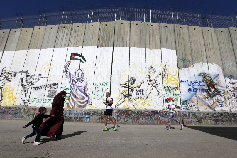 Participants run past the controversial Israeli separation barrier during the annual Right to Movement Palestine Marathon in Bethlehem, West Bank, in April. Photo: CNS/Ammar Awad, Reuters