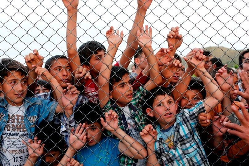Syrian children stand at a fence on 23 April at a refugee camp near Gaziantep, Turkey. Catholics should protest against immigration policies that put the lives of children at risk, said Cardinal Vincent Nichols of Westminster, England. Photo: CNS/Sedat Suna, EPA