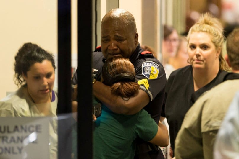A Dallas police officer is comforted at Baylor University Hospital's emergency room entrance after a shooting attack. Photo: CNS/Ting Shen, The Dallas Morning News via Reuters