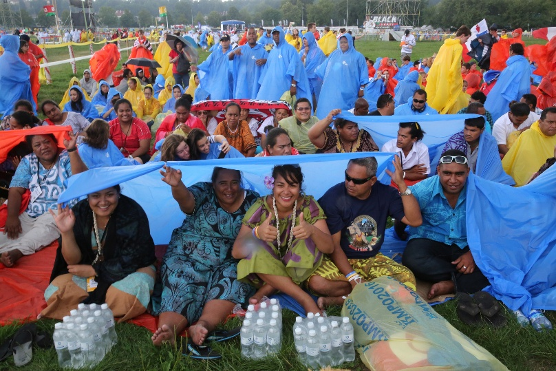 Pilgrims from the Wallis and Futuna Islands in the South Pacific take shelter during a storm at the opening Mass for World Youth Day on 26 July at Blonia Park in Krakow, Poland. Photo: CNS/Bob Roller