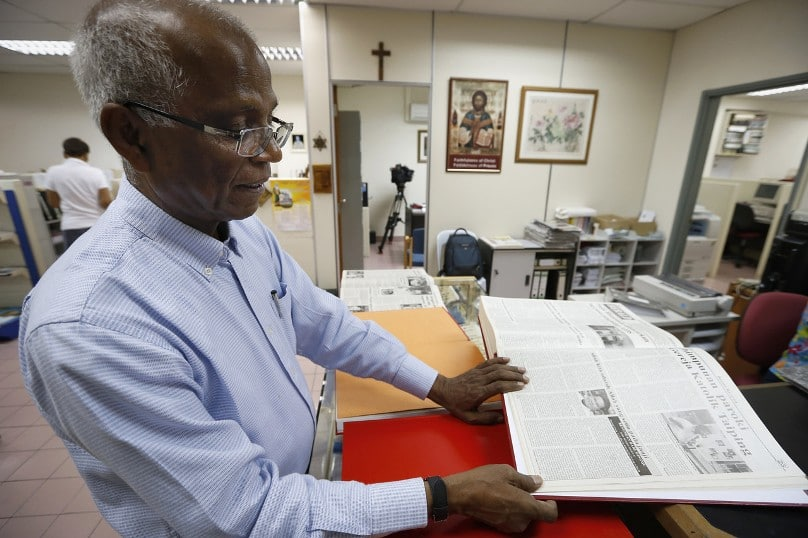 "Fr Lawrence Andrew SJ, editor of the Malaysian Catholic newspaper the Herald, shows an old edition of the weekly, which used ""Allah"" to refer to God, in 2014. Photo: Vincent Thia, AP"