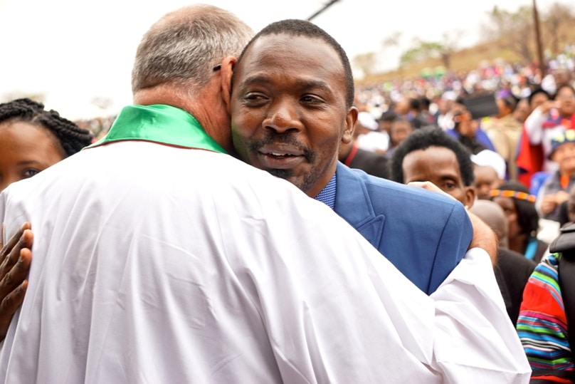 Blessed Benedict Daswa's eldest son Sammy is embraced by a priest. Photo: Jessica Braithwaite