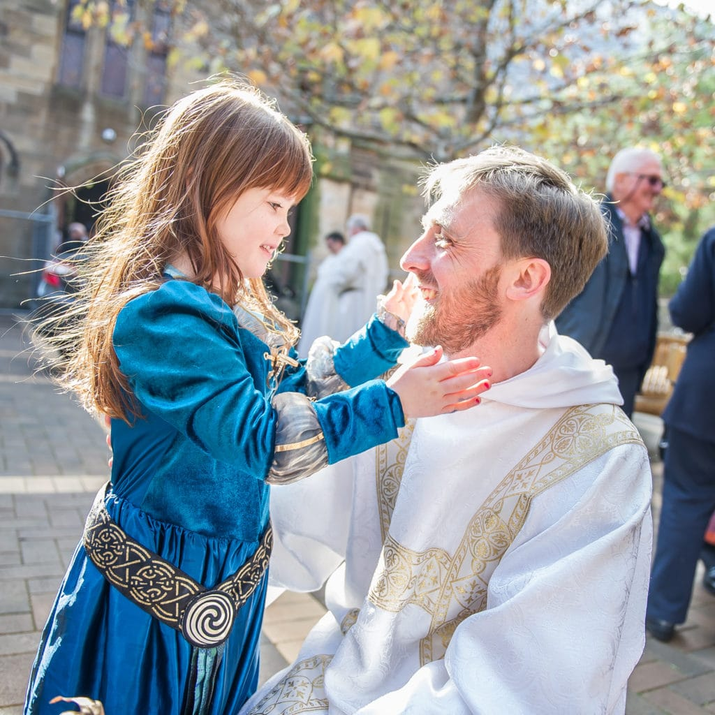 Br Matthew Boland OP is congratulated by his niece Sofia after his ordination as a deacon by the Archbishop of Sydney, Archbishop Anthony Fisher OP, at St Benedict's Church, Broadway, last weekend. Photo: Giovanni Portelli