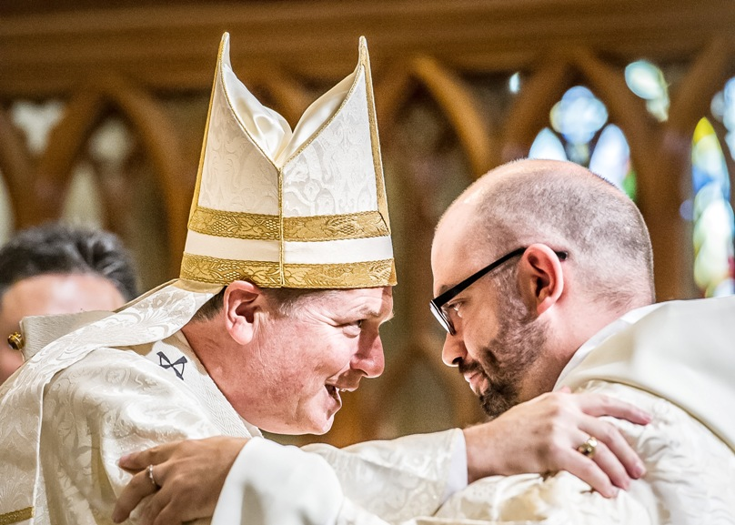 Archbishop Fisher embraces newly-ordained priest Fr Josh Miechels. Photo: Giovanni Portelli