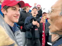 Nick Sandmann, a junior at Covington Catholic High School in Park Hills, Ky., and others students from the school stand in front of Native American Nathan Phillips. Photo: CNS photo/Kaya Taitano, social media via Reuters