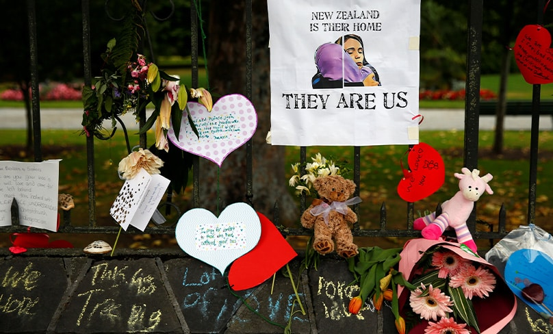 Flowers and signs are seen at the Botanic Gardens in Christchurch, New Zealand, in a makeshift memorial. Photo: CNS photo/Edgar Su, Reuters