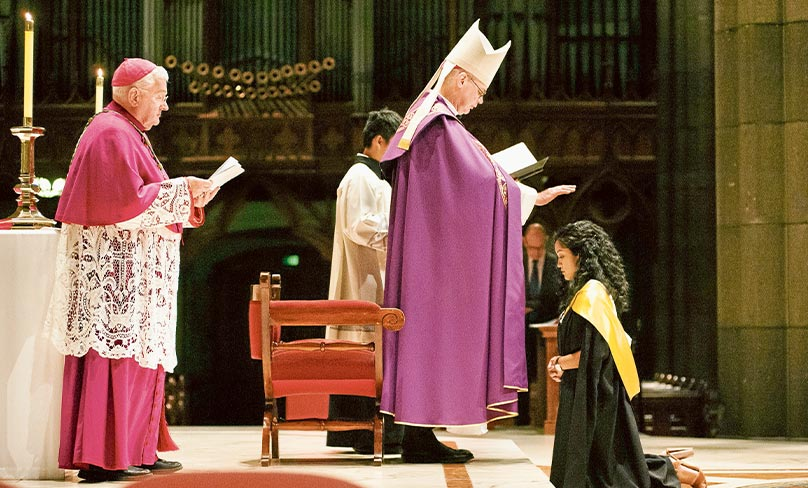 Watched by Bishop Peter Elliott, Archbishop Peter Comensoli confers a qualification upon a graduate in St Patrick's Cathedral. Photo: Peter Casamento