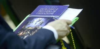 A participant holds a course textbook on exorcism and prayers of liberation.