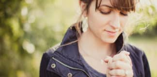Woman praying with hands together..