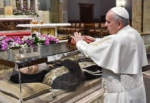 Pope Francis places a stole on a glass case containing the body of St. Pio in the Church of Santa Maria delle Grazie at the Shrine of St. Pio of Pietrelcina in San Giovanni Rotondo in Italy. Photo: CNS photo/courtesy Shrine of St. Pio of Pietrelcina
