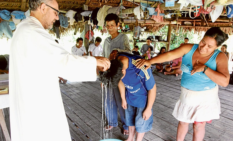 Augustinian Father Miguel Angel Cadenas baptises a young man in a village in Peru. Bishop Reyes has suggested that some priests in Rome might be useful in the Amazon. Photo: