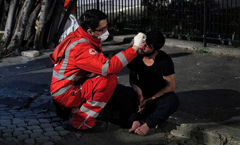 A homeless person is treated by a Red Cross worker during the COVID-19 outbreak in Rome. Photo: CNS/Guglielmo Mangiapane, Reuters