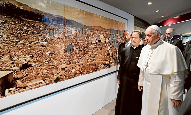 Pope Francis walks by a photo showing the destruction created by an atomic bomb during his visit to the Jesuit-run Sophia University in Tokyo. Photo: CNS/Vatican Media via Reuters