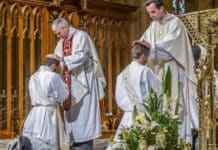 Bishop Richard Umbers and a fellow priest pray over the newly ordained. Photo: Giovanni Portelli
