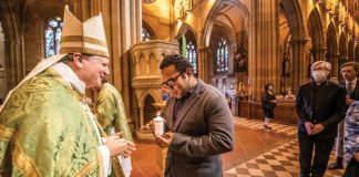 Archbishop Anthony Fisher OP hands a candle to Plenary Council delegate Chris Lee in St Mary's Cathedral. Photo: Giovanni Portelli